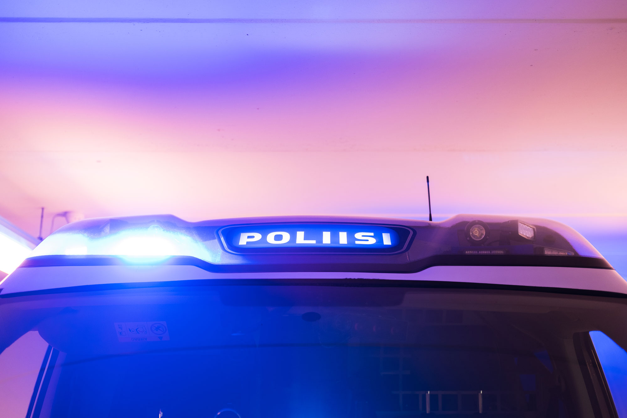The light bar of a police car with the blue light pictured against the sky.